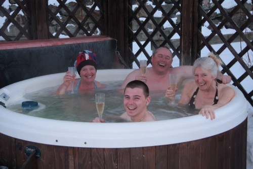 Helen and Tim enjoying a glass of Champagne in the hot tub with four-time repeat guests, Paul and Lorraine