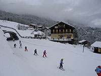 ESF childrens ski school skiing past Maison Jaune